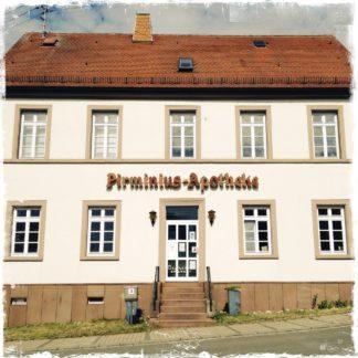 Fassade einer alten Apotheke mit Fenstern, Tür, Treppe, rotem Dach an schräger Straße. Schriftzug Pirminius-Apotheke über dem Eingang.