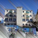 Front eines weißen Mehrfasmilienhauses, innerstädisch aus der Froschperspektive betrachtet. Parkplatzschilder an einer bildbreiten Treppe führen den Blick zur strichlierten im 45 Grad Winkel abstrahierten Hausfront. Überm Flachdach blauer Himmel.