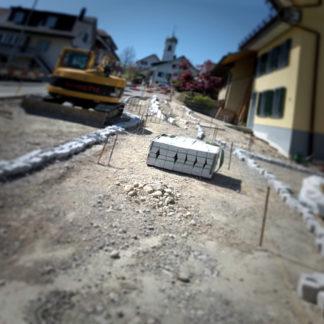 Wie in einem Hoorofilm zeigt sich eine Baustelle einer aufgerissenen Dorfstraße nebst Bagger. Unscharfe Vignette und schräge Bildeinstellung erzeugen den Unheimlicheffekt.
