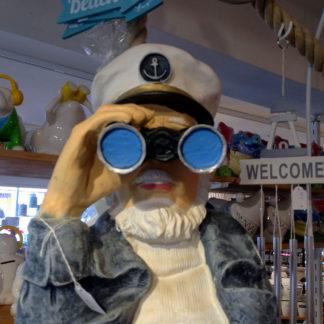 Büste eines Seemanns mit Kapitänsmütze, der durch ein Fernglas mit blau gemaltem Glas schaut. Im Hintergrund des offenbaren Souvenirsladens das Schild Welcome und weitere Gegenstände mt Souvenirscharakter.