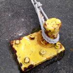 An einem geblen Stutzen ist das Tau eines offenbaren Schiffs verankert. Sechs dicke Schrauben halten den Poller im Teer fest.