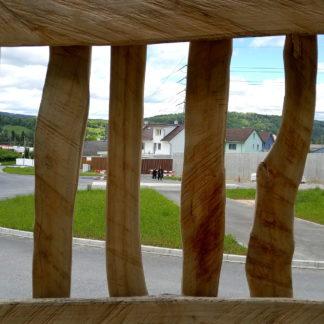 Blick durch einen halbgesägten Bohlenzaun mit unregelmäßiger natürlicher Astkrümmung. Im Hintergrund durch die Ritzen erkennt man Menschen vor Häusern.