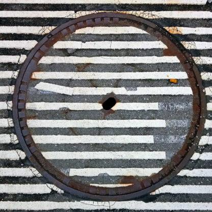 Weiße Straßenmarkierungen, kaum fünf Zentimeter breit zieren wulstig eine geteerte Straße, zentral ein Kanaldeckel, auf dem sich die Streifen fortsetzen, aber teils beschädigt sind.