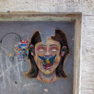 Aus dem Mund eines etwas unproportionalen Portraits einer Frau fliegt ein schillernder Paradiesvogel. Das Graffito ist in einem zugemauerten Fenster an einer Wand mit Kreide gemalt.