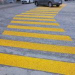 Bildfüllender gelber Zebrastreifen, der sich nach rechts knickt. Ganz oben Reifen und unterer Teil eines grauen und eines weißen PKWs, die die Straße queren.