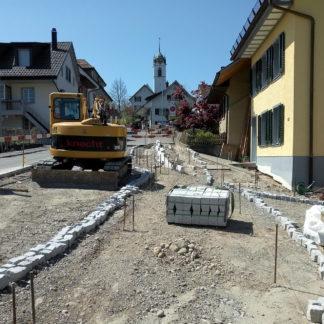 Eine ruhende Baustelle, klare Darstellung ohne Bildbearbeitungseffekte. Auf eine Kirche führt die in Arbeit befindliche Dorfstraße hinzu. Ein Bagger mit der Aufschrift Knecht zur linken. Die Wegbegrenzungen sind mit Stahlstäben und grob gelegten Pflastersteinen angedeutet.