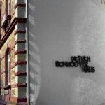 Die Aufschrift Dietrich Bonhoefer Haus aus gusseisernen schwarzen Lettern an der weißen Wand einer Hausecke, die günstig vom Licht und Schatten der gezackten Mauerecke und Dachrinne gestreift wird und somit eine unvermutete Tiefe erfährt.