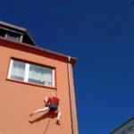 Kunststoffigur lebensgroß an rosarötlicher Hauswand unter stark gesättigtem blauem Himmel. Die Kleterin in kurzer Sportkletterkleidung kraxelt waghalsig unter einem Vorhang behangenen Fenster.