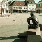 Ein großer Platz. Im Vordergrund sitzt eine Bronzefigur im Halbprofil mit dem Rücken zum Betrachter, zur Betrachterin auf einem fein gesägten Sandstein. Die Figur trägt die Kleidung eines Gepäcktransporteurs der Jahrhundertwende 19. zu 20. Jh.
