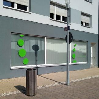 Lamellenverhangenes Schaufenster im Erdgeschoss eines innerstädtischen, modernen Bauwerks. Ein Straßenschild nebst Laterne wirft Schatten von rechts. Grüne Punkte kleben auf den Scheiben. Vorne ein öffentlicher Straßenmülleimer.
