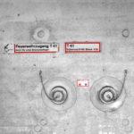 Eine Betonwand, aus der die Stutzen für Löschschlauchanschlüsse wie Augen herausschauen. Die Schraubverschlüsse sind mit Ketten befestigt, was ein bisschen wie Augenschminke wirkt. Zur Stirn zwei rot umrandete Schilder mit Aufschrift Feuerwehrzugang T 41.