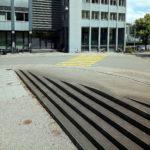 Weitläufige Außentreppe im unteren Teil des Bildes läuft längst zu einem gelben Zebrastreifen vor einem Geschäftsgebäude. Ein paar Mopeds und Fahrräder stehen auf dem Gehweg