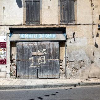 """Eine längliches Schild mit der Aufschrift """"Un Certain Ragard"""" prangt über einem hölzernen Tor. Eine Schnur mit Wimpeln, die offenbar über die Straße gespannt ist, wirft einen Schatten. Am Tor ein fernöstliches Schriftzeichen-Graffito."""
