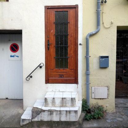 eine Steile, enge, weiß gekachelte, dreistufige Haustreppe führt zu einer braunen Tür, deren Kern verglast und vergittert ist. Daneben ein Regenfallrohr, ein Briefkasten und die Einfahrten zu Nachbargaragen.