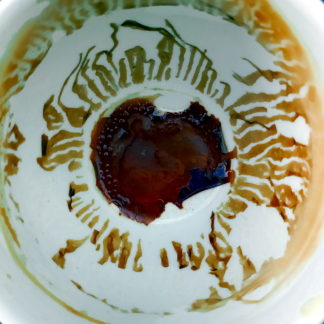 Ziemlich abstrakte runde Struktur, aus der man gewillt sein mag, Schriftzeichen im fernöstlichen oder israelischen Stil zu lesen. Das dunkle Zentrum gibt endlich Aufschluss, dass es sich bei der Szene um den Blick in eine leergetrunkene Kaffeetasse handelt.