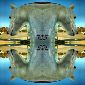 Der kunststoffene Kopf einer Pferdestatue ist vierfach gespiegelt und bildet eine regelmäßige Struktur vor städtischer Szene und unter und über blauem Himmel. Durch das Ineinanderkopieren werden Schriftzeichen auf dem Hals des Pferdes zur Zahl 25, bzw. 52, da auch die Zahl vierfach gespiegelt wird.