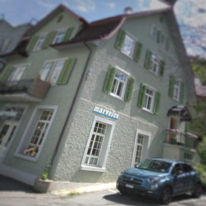 """Ein typisches schweizerisches Stadthaus, das in unscharfer Vignette und schräg abgebildet einen Horror-Haus-Touch erhält. Der Schriftzug """"marvelos"""" über einem Fenster im Erdgeschoss deutet an, dass sich ein Fahrradladen hinter den Mauern verbirgt. Vorm betreppten Hauseingang steht ein blaues Auto zeitgenössicher Bauart."""