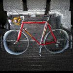 Verfremdetes Bild eines roten Rennrads der Marke Jungherz. Strahlenförmig bewegt sich die Struktur des Bildes auf den Betrachter, die Betrachterin zu. Die Reifen strahlen weiß.