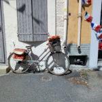 Fahrrad mit Geranienkörbchen auf Frontgepäckträger lehnt an einer Hauswand. Eine Schnur mit vielen französischen Fähnchen baumelt rechts im Bild an einer Regenfallrinne. wie ein Männchen schaut aus einem Kellerfenster die Konstruktion der Heizölbetankung. Ein Fensterladen ist geschlossen.