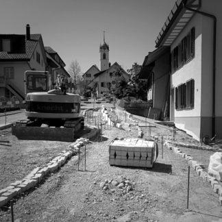 Aufgerissene Dorfstraße, die auf eine Kirche hinzu führt. Die Ränder der Straße sind mit Pflastersteinen provisorisch gelegt, Links ein Bagger. Viele Eisenstäber und Schnüre zeigen die Bauvermessung. Niemand arbeitet.
