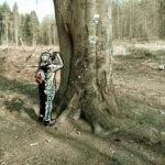 Eine Buche und eine Eiche mit zwei dicken Stämmen teilen sich einen Standort, sind zusammengewachsen. Die Rinde der Buche ist vielfach geritzt mit Namen und Datumsangaben. Ein Naturschutzschild, dreieckig mit grünem Rand, hängt an dem Naturdenkmal. Links neben dem Baum die verfremdete Silhouette einer Person, die das Denkmal mit dem Smartphone fotografiert.