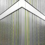 Moderne Fassade auf die Hausecke fokussiert. Graue metallisch glänzende Elemente werden senkrecht gebrochen von grünen Fugen. Eine horizontal verlaufende Fläche unterbricht die senkrechten Elemente und lässt die Szene pfeilförmig wirken.