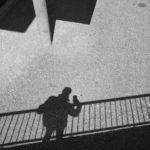Der Schatten eines Menschen, der mit dem Handy fotografiert und an einem Geländer lehnt. Nur teer und Schatten und im Ansatz eine schmale runde Säule, die wiederum Schatten wirft.