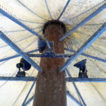 Blick von unten auf eine Stahlstütze, die mit eisernen Armen eine Art Schirm trägt. Auf den Querarmen befinden sich Stacheln, um Tauben zu vergrämen. Leuchten sind angebracht. Viele Spinnweben umgarnen die Konstruktion.