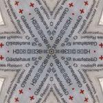 Kaleidoskopisch gespiegelte Schrift bildet einen schwarz weiß strukturierten Stern. Rote Kreuz-Kreuze an den Rändern. Man kann die Wotre Gästehaus und Betreutes Reisen lesen, die an den Nahtstellen zu einer Phantasieschrift verschmelzen, die an Khmer-Schrift erinnern.