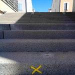 Mindestens drei Viertel der Szene wird von Betontreppenstufen dominiert. Auf der untersten Stufe ist ein gelbes Kreuz gemalt. Das Bild verliert sich am oberen Rand im hellen Blau des Himmels, der von Hauswänden flankiert wird.
