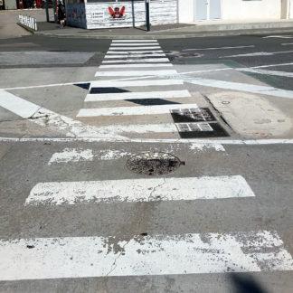 die unteren acht zehntel des Bilds sind eine Draufsicht auf eine Straße. ominiert vom Zebrastreifen und ihn brechenden Linien und Kanal- und Technikdeckeln. Am oberen Bildrand bleckt ein rotes Graffito auf einer Hauswand.