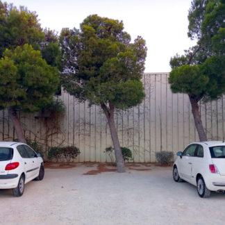 Zwischen zwei weißen Autos ist eine Lücke auf einem offenbaren Parkplatz vor einer lammelen-Metallwand. Pinien und deren Nadeln am Boden deuten auf einen mediterranen Ort hin.