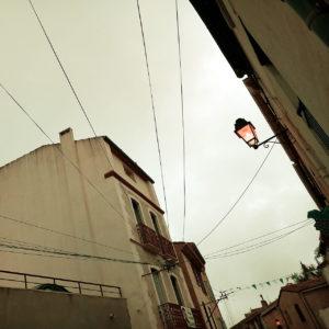 Blick aufwärts aus einer offenbar südländischen Dorfgasse auf die zwischen Häusern gespannten Strom- und Telekommunikationsverkabelungen, die wie ein spartanisch ausgestattetes Spinnennetz wirken. An der Hauswand rechts kragt eine verierte eiserne Straßenlaterne aus. Sie leuchtet gelb. Der Himmel ist milchig und noch recht hell.