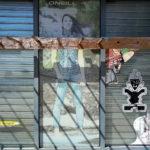 Hinter einer Holzkonstruktion, die sich waagrecht durchs Bild ziehtund an der hölzerne Stäbe hervorragen wie bei einem Holzrechen, ist ein Ganzkörper-Werbeplakat eine jungen, jeanstragenden Frau zu erkennen. Weitere Aufkleber daneben zeigen mystische Figuren wie mexikanische Geisterfiguren. Ein Schattenwurf von den Holzstäben gibt der Wand eine Struktur.