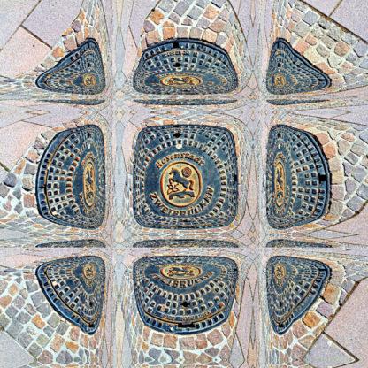 Draufsicht auf einen per Bildbearbeitung zu einer abgerundeten Quadratvorm gemachten Kanaldeckel mit der Aufschrift Rosenstadt Zweibrücken und einem springenden Ross und eine Rose als Motiv. Ringsum Kopfsteinpflaster, ebenso in einer merkwürdige Form gezwungen.