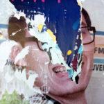 Zerfetztes Plakat zeigt ein Gesicht mit Brille, dessen Mitte durch den Abriss die dahinter liegenden Plakate als zackige nach unten zeigende Form teilt. Grundfarben dunkelblau und hautfarben.