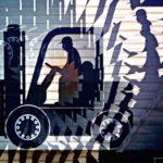 Wie ein zerschnittenes und neu zusammengesetztes Papierbild erkennt man einen sternförmig verschobenen Gabelstapler als Silhouette, von rechts nach links im Profil fahrend.