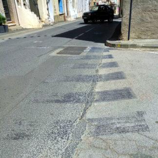 Gesenkter Blick auf eine Straße, von der der Zebrastreifen entfernt wurde und dessen Markierung noch grau in grau durchscheint. Am oberen Bildrand biegt ein Geländewagen im Schatten eines Hauses in die Straße ein.