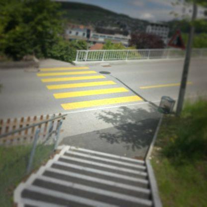 Treppab mündet der Fußweg auf einer Straße und wird dem Rhythmus der Treppe genüge tragend von einem gelben Zebrastreifen fortgesetzt bis zur Kante der Hangstraße. Im Hintergrund ahnt man die Stadt. Vignette vernebelt die Szene und verleiht ihr einen mystisch-verträumten Hauch.