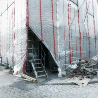 Dreieckig bleckt der Eingang zu einem Baugerüst, verhangen von Plastikplanen. Eine Leiter führt ins Dunkel hinter den Planen der Gebäudeecke.