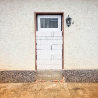 In einer weißen Wand wurde eine offenbare ehemalige Haustür bis zu vier Fünfteln zugemauert mit weißen Gasbetonsteinen. Das obere Fünftel ist ein Fensterchen. rechts neben dem Ensemble hängt noch die Hauslaterne und eine winzige Hausnummer 4.